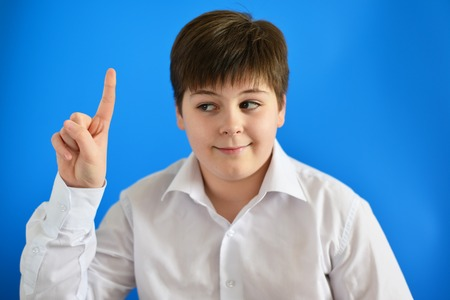 he: Teen boy holding his finger up, he came up with the idea Stock Photo