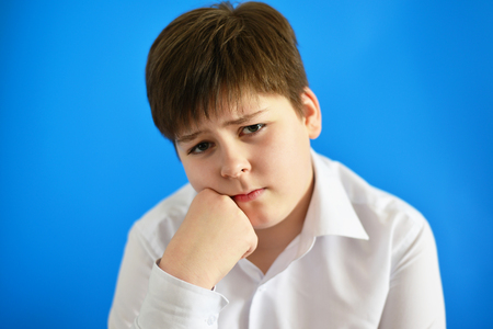 chagrin: Pensive teenage boy on a blue background
