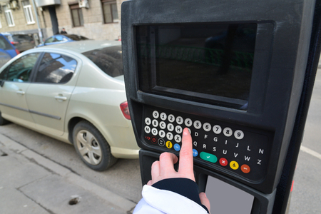 enters: Moscow, Russia - March 14, 2016. Womans hand enters the data in the parking payment machine