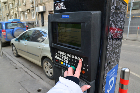 transfers: Moscow, Russia - March 14, 2016. Womans hand enters the data in the parking payment machine