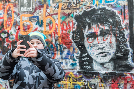 cult: Moscow, Russia - February 21.2016. Fans are photographed against a wall dedicated to the memory of the cult singer Viktor Tsoi