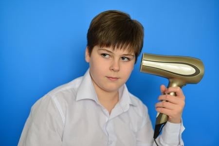 accosting: Boy teenager dries hair the hair dryer