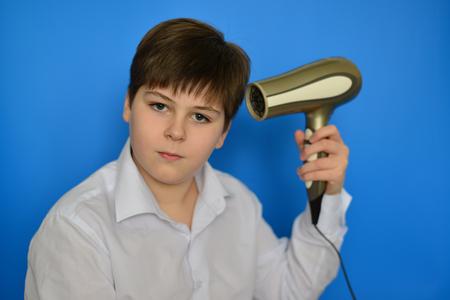 secador de pelo: Adolescente del muchacho que el cabello seco el secador de pelo Foto de archivo