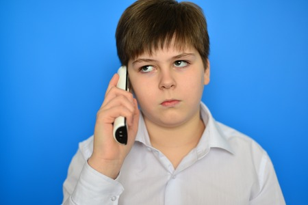 pert: Teen boy talking by a radiotelephony on a blue background Stock Photo