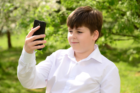 12 13: Teen boy talking on the phone outdoors Stock Photo