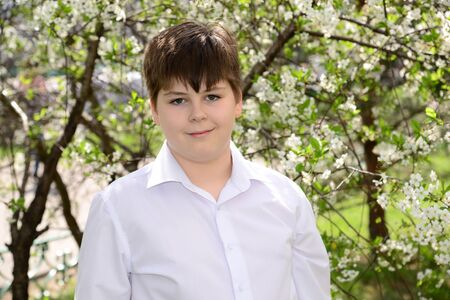 12 13 years: Portrait of a boy teenager in a spring garden