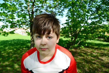 12 13 years: funny teenager boy looks into the camera in summer park