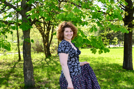 40 year old woman: woman standing in the park near the chestnut Stock Photo