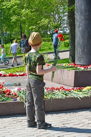 marshal: Zelenograd, Russia - May 09.2016. Little boy laying flowers at the monument to Marshal Rokossovsky in Victory Park