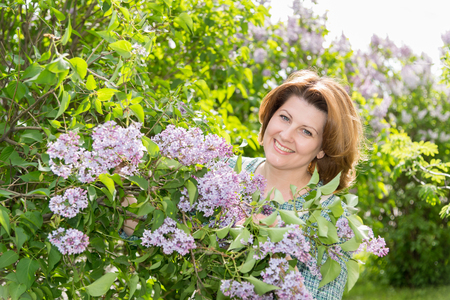Adult woman in a park near the blossoming lilac
