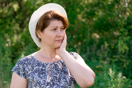 melancholia: thoughtful Woman in a summer hat on nature
