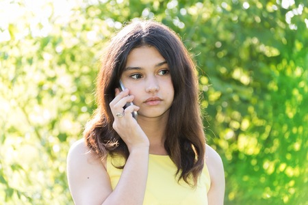 Sad girl talking on the phone in the park