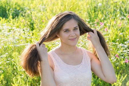 teeny: girl holding long hair on a flower meadow Stock Photo