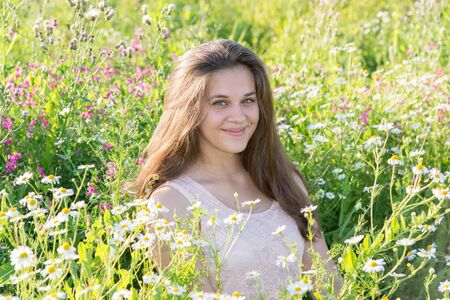 teeny: girl sits on a meadow with wild flowers