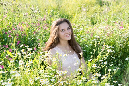 sits: girl sits on a meadow with wild flowers