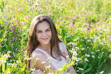 Beautiful long-haired girl on a glade with meadow flowers