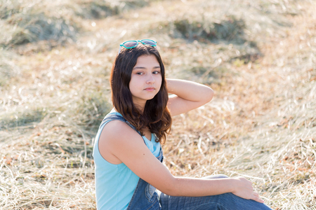 teeny: Portrait of teen girl in a field with straw