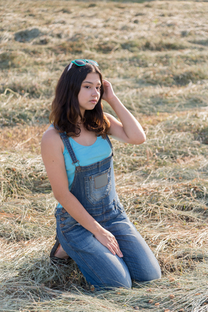 Beautiful teen girl in a field with straw