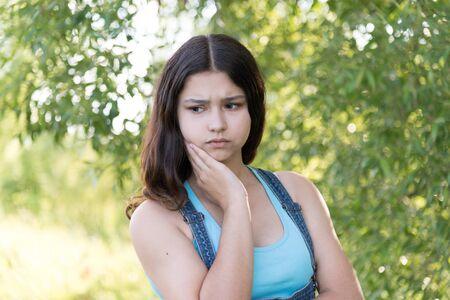 teeny: Portrait of a sad teen girl on nature Stock Photo