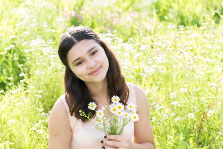 teeny: Girl teenager with bouquet of daisies on a summer meadow Stock Photo