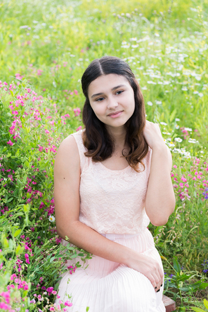 teeny: Pretty girl sits on a richly meadow Stock Photo