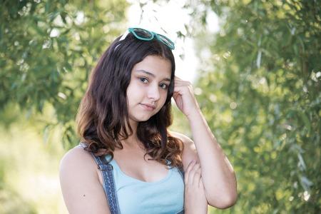 teeny: A Teen girl standing near the tree