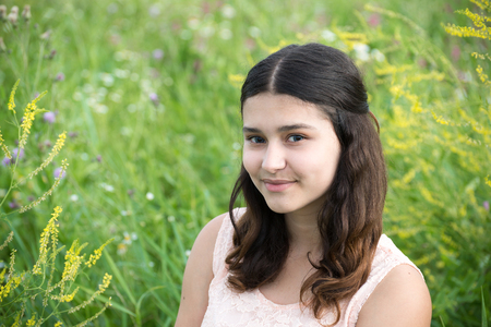 teeny: The girl with dark hair on a background of green grass Stock Photo