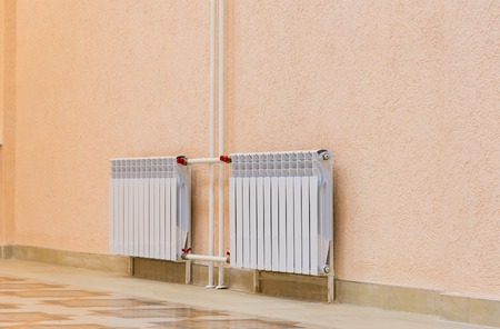 convection: White new radiator on a pink wall