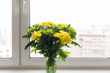 wonderfull: Bouquet of yellow chrysanthemums and green stands on the windowsill Stock Photo