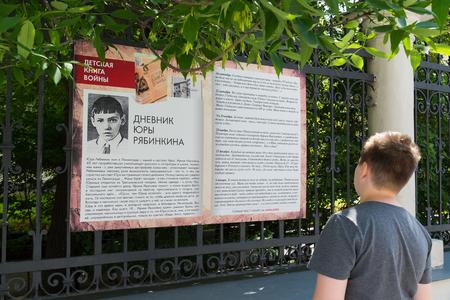 Moscow, Russia - June 02.2016. Teen boy reading a fragment of a children's book of war on Myasnitskaya Street