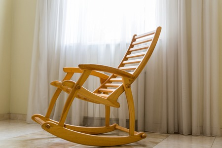 Wooden rocking chair near the window in the room