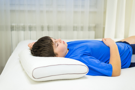 Boy teenager sleeping on an anatomic pillow