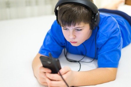 12 13: Teen using cell phone with a headphones