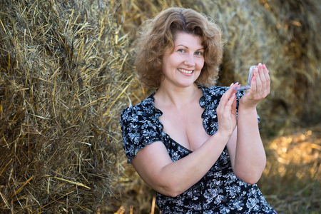oneself: Woman powder oneself woman in a field on a background of straw bales