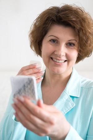 Woman puts makeup on the face of yourself Stock Photo