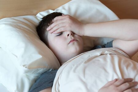 accosting: boy with headache lying in bed