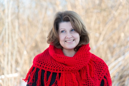 Beautiful woman with red knitted shawl on the shoulders of the outside Stock Photo