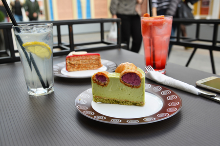 pistachio: piece of pistachio cake with profiteroles on the table of a street cafe