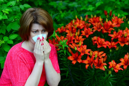 handkerchief: A woman with an allergic rhinitis near lilies in nature