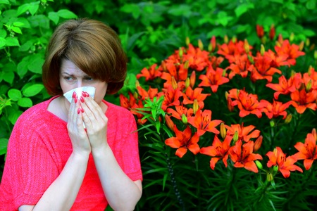 woman with an allergic rhinitis near lilies in nature