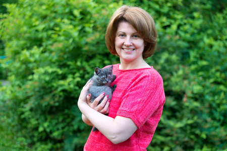 Vrouw die een blauwe katjes Schotse Straat in openlucht koestert