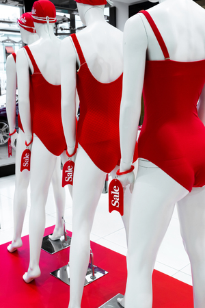 A series of mannequins in red swimsuits.Sale Banco de Imagens