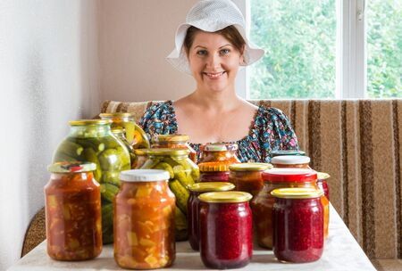 Housewife with canned vegetables and berries in a cans