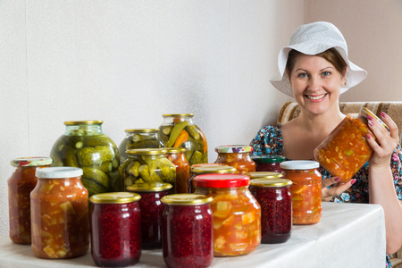 woman sits at table with homemade canned vegetables and jam