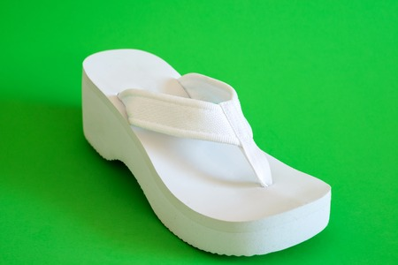White female beach shoes on a green background