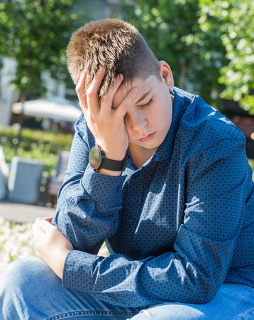 Droevige tiener zit op straat