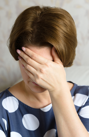 Frustrated woman sits covering her face with her hand