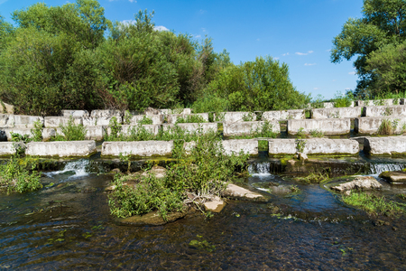 Concrete blocks lying on a small river - dam