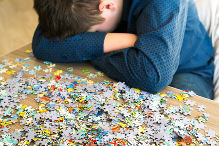Tired teenager is sitting tilting his head next to the puzzles