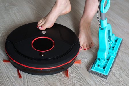 woman includes a robotic vacuum cleaner and holds mop